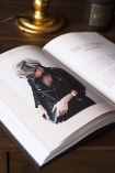 Lifestyle image of the All Black Everything book open with an image on wooden coffee table with gold table lamp base
