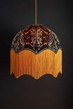 lifestyle image of Anna Hayman Designs Siouxsie Lamp Shade lit up on dark blue wall background