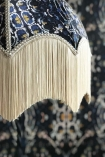 detail image of fringe on Anna Hayman Designs Siouxsie Lamp Shade with matching wallpaper backgroundHayman Designs Siouxsie Lamp Shade