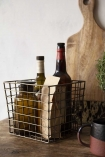 Lifestyle image of the Antique Brass Coloured Wire Utility Basket filled with wine bottles and on a corwded shelf
