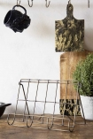 Lifestyle image of the Antique Brass Finish Wire Cookbook Holder without a cookbook on a crowded wooden shelf