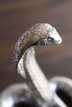Close-up detail image of the head of the Antique Silver Cobra Snake Ornament with dark wooden background