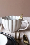 lifestyle image of Antique White Chateau Mug with Brass Peacock Spoon inside and tableware in forefround on pale wooden surface and pale wall background