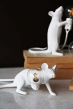 lifestyle image of Aramis The Crouching Mouseketeer Lamp - White turned on marble surface with pile of books and second mouse lamp in background