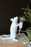 lifestyle image of Athos The Standing Mouseketeer Lamp - White turned off on open book with house plant and dark wall background