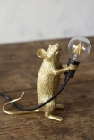 Lifestyle image of Athos The Standing Mouseketeer Lamp - Gold turned off on wooden table and pale wall background