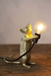 Lifestyle image of Athos The Standing Mouseketeer Lamp - Gold lit up on wooden table and pale wall background