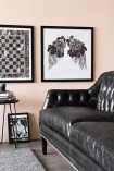 Lifestyle image of Black Leather Chesterfield 3 Seater Sofa with painting hung on wall and black side table on grey rug