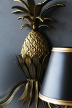 detail  image of Gold Pineapple Wall Light hung on dark grey wall