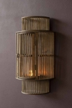 lifestyle image of the Bamboo Curved Wall Lantern with a candle lit inside it on briarwood painted wall background
