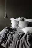 lifestyle image of Lisbon Soft Linen Duvet Cover - Grey on bed with white and grey pillows and black ceiling light with dark grey wall background
