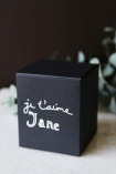 detail image of box of Bella Freud Je T'aime Jane Candle on marble counter with eucalyptus in background and dark wall background