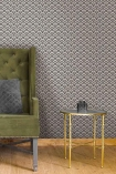 Lifestyle image of the Betsy Fan Ditsy Smoke Wallpaper by Pearl Lowe with gold side table, green armchair and wooden flooring