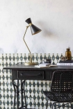 Front-on lifestyle image of the Black Metal Sideboard Desk with table lamp and chair with patterned wallpapered background