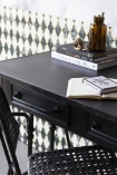 Close-up detail lifestyle image of the Black Metal Sideboard Desk with desk accessories and patterned wallpaper background