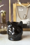 Lifestyle image of the Black Cat Candle Holder without a candle in it with small vase and picture frame on marble console table with dark wall background