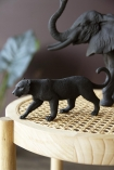 Lifestyle image of the Black Stalking Leopard Ornament with the Black Bull Elephant Ornament in the background on wooden and woven stool