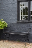 Side on view of the Industrial-Style Black Metal Two-Seater Bench in an outdoor setting on a black brick wall with plant and window