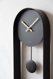 detail angled image of the Modern Black & Brass Pendulum Clock face on white wall background