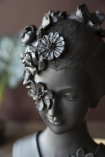 Close-up detail image of the Beautiful Black Geisha Bust With Floral Headdress with plant in background and dark wall