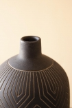 Close-up detail image of the neck on the Black African Ceramic Bottle Vase with pale wall background