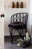 lifestyle image of Black Bamboo Chair With Velvet Seat Pad with apothecary jars and plants on black tiled floor and white wall background