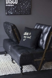 Side angle lifestyle image of the Black Leather Loveseat Sofa with alternate backs and a cushion