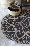 lifestyle image of Black Mandala Pattern Natural Jute Circular Rug with wicker baskets with pom poms and grey patterned flooring background