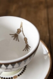 detail image of the illustration on inside of cup of Sleeping Face Teacup & Saucer on wooden table background