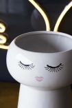 detail image of the rim of Sleeping Face Flower Pot on dark surface with LED Angel Wings Neon Light in background