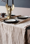 detail image of Blush Pink Woven Linen Tablecloth with tableware and Phoenix Candle Holder with contrasting wall background