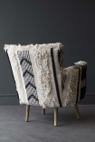 lifestyle image of back of Boho Woven Armchair on grey flooring and dark grey wall background