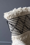detail image of top of Boho Woven Armchair on dark grey wall background