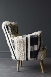 lifestyle image of side view of Boho Woven Armchair on grey flooring and dark grey wall background