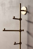 Close-up detail image of the Light Gold Vertical Coat Rack With Swivelling Pegs on dark wall background