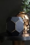lifestyle image of Honeycomb Jewel Vase - Black with copper vase with plant in on black side table and dark wall background