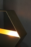 detail image of light on Hexagonal Brass Table Lamp lit up with dark wall background