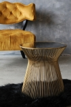 lifestyle image of Hampstead Gold Side Table with Cloud Velvet Chair - Golden Glow behind and black sheepskin with distressed grey wall background