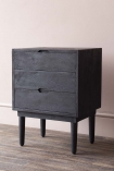 lifestyle image of Bureau-Style Black Mango Wood Bedside Table with lid closed on wooden flooring and pale pink wall background