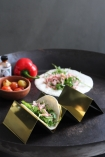 lifestyle image of Gold Metal Kitchen Stand with taco inside on black table with red pepper and other foods on it