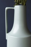 detail image of handle on Ceramic Bottleneck Vase With Handle - Pale Green with plants inside on dark blue wall background