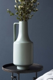 lifestyle image of Ceramic Bottleneck Vase With Handle - Pale Green with plants inside on black tray side table with dark blue wall background