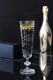 lifestyle image of Ritzenhoff Champagne Flute - Nerodiseppia with black and gold messy writing on and box and gold champagne bottle in background on black table