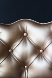 detail image of seat on Cloud Faux Leather Chair - Metallic Gold with dark wall background