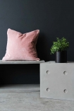 lifestyle image of Lyon Beton Concrete Dice StoolTable - Available In 2 Sizes with pink pillow and plant in pot on top with dark wall background