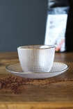 lifestyle image of Clear Glass Cup & Saucer on wooden table with black bag of coffee