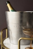 Close-up detail lifestyle image of the Rustic Cuvee De Prestige Champagne / Wine Cooler with bottle inside on marble and gold drinks troley with champagne glass and dark wall background