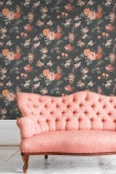 Lifestyle image of the Dawn Chorus Noir Black Wallpaper by Pearl Lowe with pink cushioned sofa