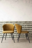 Lifestyle image of two Golden Ochre Deco Velvet Dining Chair together with patterned wallpaper background and pale grey flooring