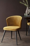 Front-on lifestyle image of the Golden Ochre Deco Velvet Dining Chair with dark brown wall background and dark wooden fooring
